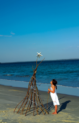 Girl on beach looking at driftwood Christmas Tree with star